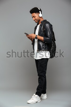 Cheerful african american man with beard in black hat  Stock photo © deandrobot