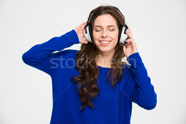 Smiling inspired young woman with closed eyes listening to music Stock photo © deandrobot
