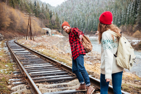 Couple reaching hands and waking on railroad in mountains Stock photo © deandrobot