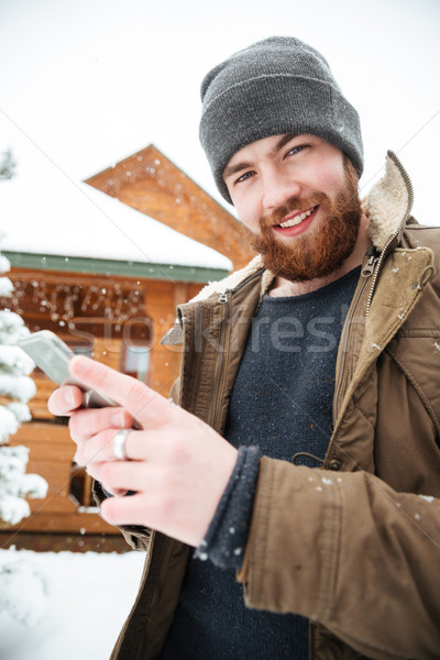Cheerful man using mobile phone in winter  Stock photo © deandrobot