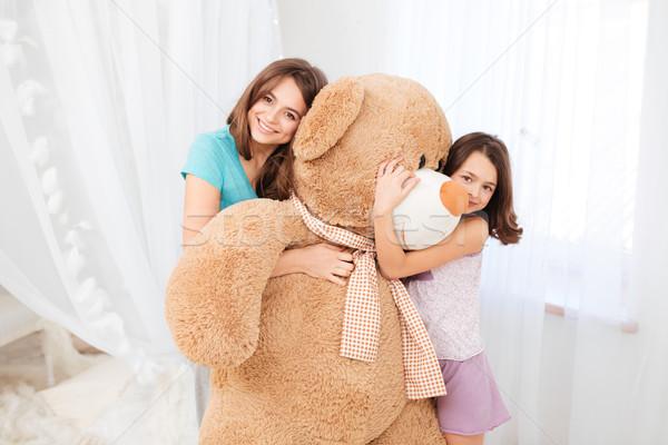 Two beautiful happy girls embracing huge plush bear  Stock photo © deandrobot