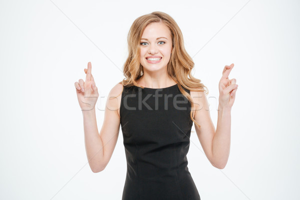 Woman standing with crossed fingers Stock photo © deandrobot
