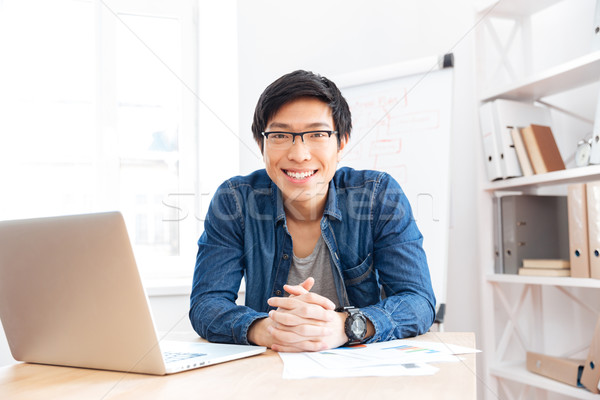 Cheerful businessman working with laptop on workplace Stock photo © deandrobot