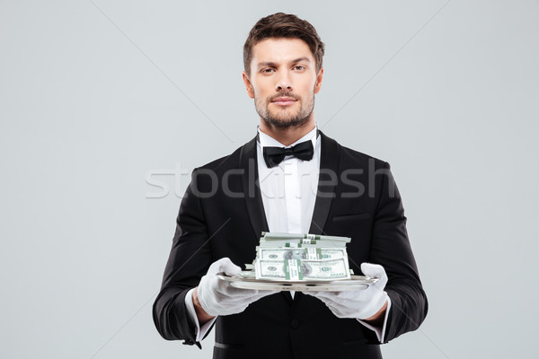Attractive butler in tuxedo and gloves holding money on tray Stock photo © deandrobot