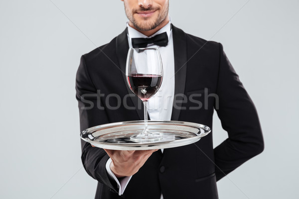 Butler in tuxedo holding silver tray with glass of wine Stock photo © deandrobot