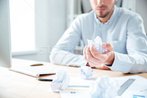 Businessman sitting in office and holding crumpled paper Stock photo © deandrobot