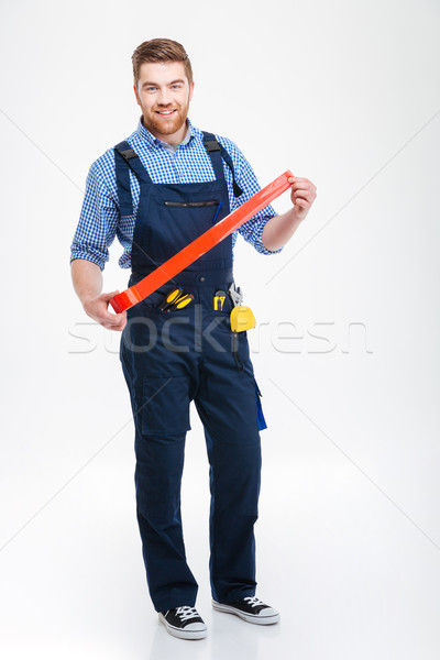 Happy bearded worker standing and using red adhesive tape Stock photo © deandrobot