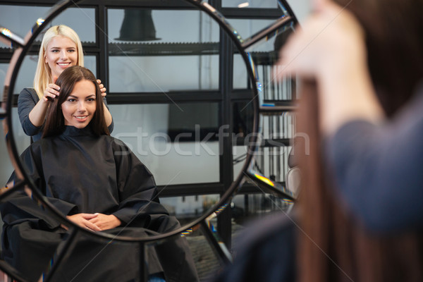 Mirror reflection of woman getting her haircut by stylist Stock photo © deandrobot