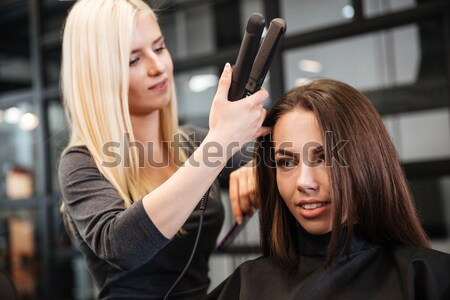 Hairstylist curling hair woman client in hairdressing beauty salon Stock photo © deandrobot