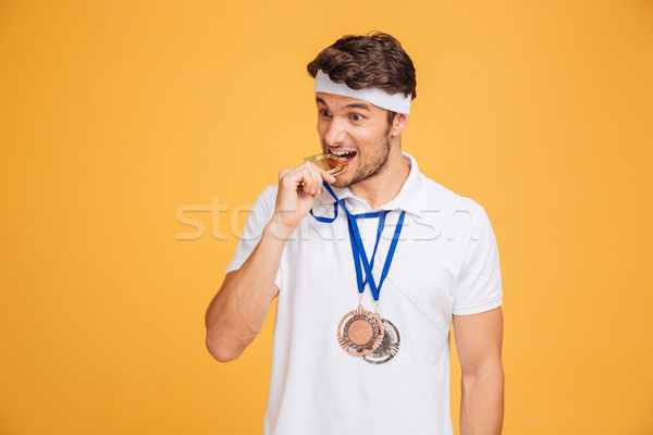 Primo piano bello giovane atleta mordere medaglia Foto d'archivio © deandrobot