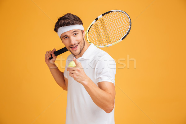 Happy man tennis player holding racket and pointing on you Stock photo © deandrobot