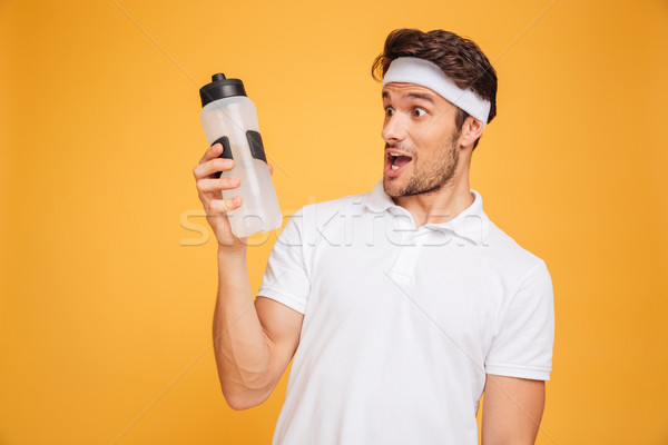 Portrait of amazed sportsman looking at water bottle Stock photo © deandrobot