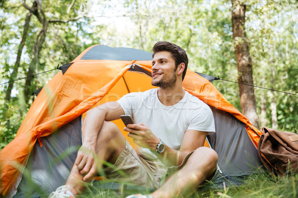 Man tourist using smartphone sitting in touristic tent at forest Stock photo © deandrobot