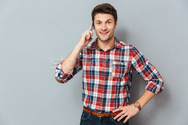Smiling handsome young man standing and talking on cell phone Stock photo © deandrobot