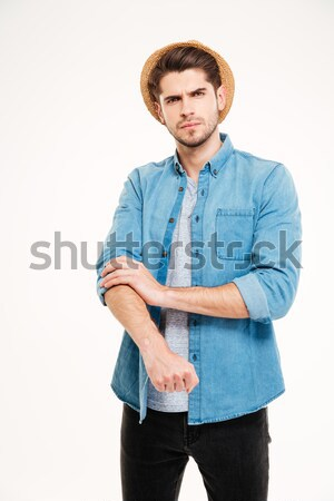 Serious handsome young man standing and rolling up his sleeves Stock photo © deandrobot