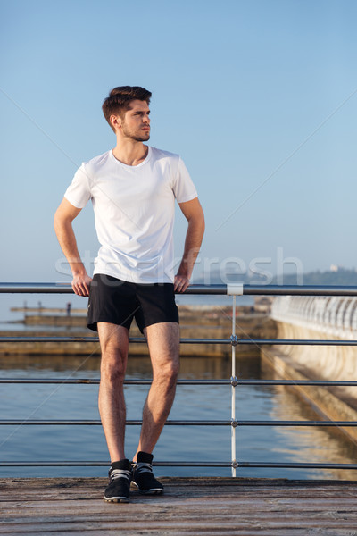Pensive young sportsman standing and thinking on pier Stock photo © deandrobot