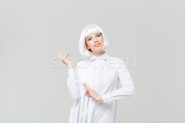 Smiling beautiful young woman standing and gesturing Stock photo © deandrobot