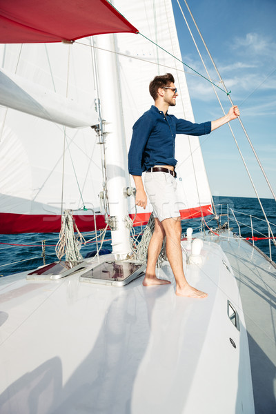 Stock photo: Young bearded man standing on a yacht
