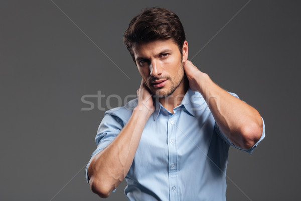 Confident young businessman in blue shirt touching his neck Stock photo © deandrobot
