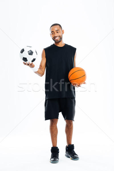 Portrait of a smiling sports man looking at soccer ball Stock photo © deandrobot