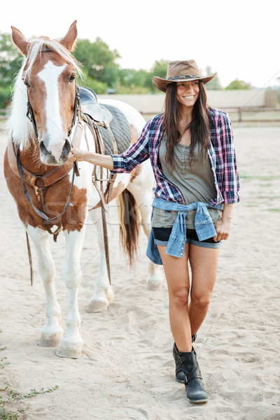 Cowboy girl taking her horse for a walk Stock photo © deandrobot