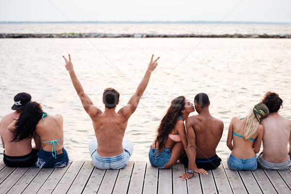 Szczęśliwy pary posiedzenia molo morza Zdjęcia stock © deandrobot