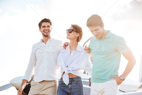 Cheerful young people standing on runway in front of airplane Stock photo © deandrobot