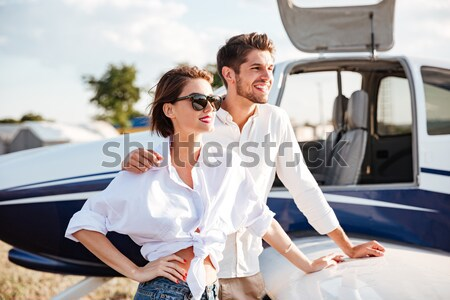 Young pilot and beautiful stewardess sitting inside airplane cabin Stock photo © deandrobot