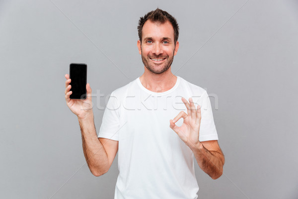 Szczęśliwy przypadkowy człowiek smartphone ekranu Zdjęcia stock © deandrobot