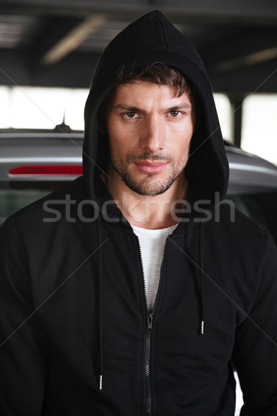 Serious young man in black hoodie Stock photo © deandrobot