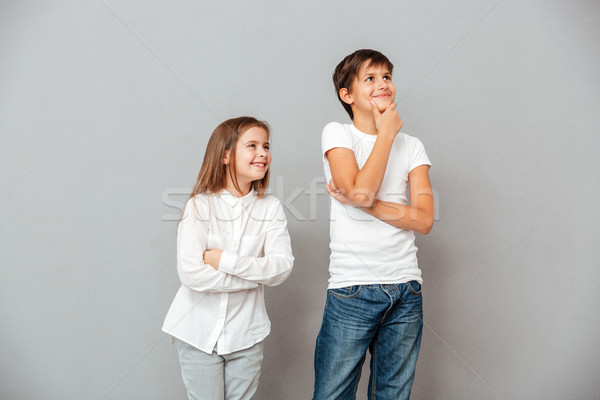 Two happy pensive children standing and looking away Stock photo © deandrobot