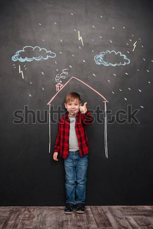 Kid standing in house on chalkboard while holding flower Stock photo © deandrobot