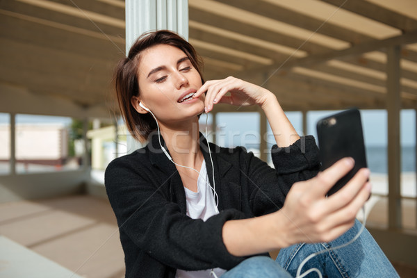 Happy woman listening to music from smartphone on the beach Stock photo © deandrobot