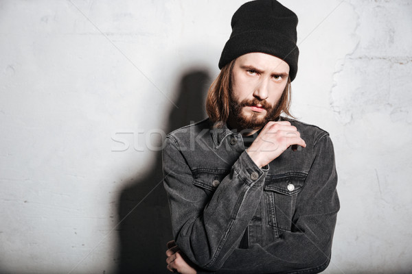 Pensive hipster guy in hat looking at camera Stock photo © deandrobot