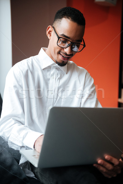 Happy african businessman wearing glasses coworking. Stock photo © deandrobot