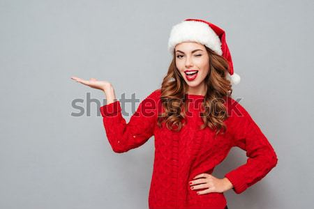 Smiling attractive young woman in santa hat and red sweater Stock photo © deandrobot