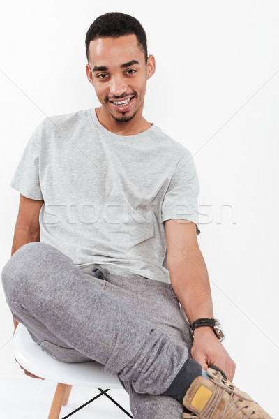 Happy young dark skinned man sitting over white background Stock photo © deandrobot