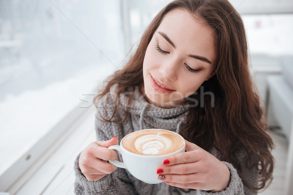 Attractive young lady dressed in sweater sitting in cafe Stock photo © deandrobot