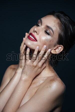Beautiful young woman with shimmering makeup touching her face Stock photo © deandrobot
