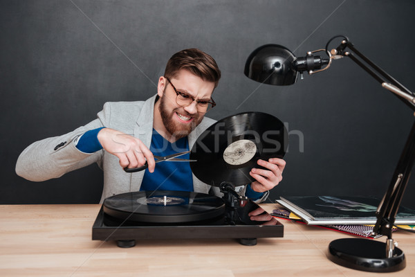 Mad irritated man sitting and cutting vinyl record with scissors Stock photo © deandrobot