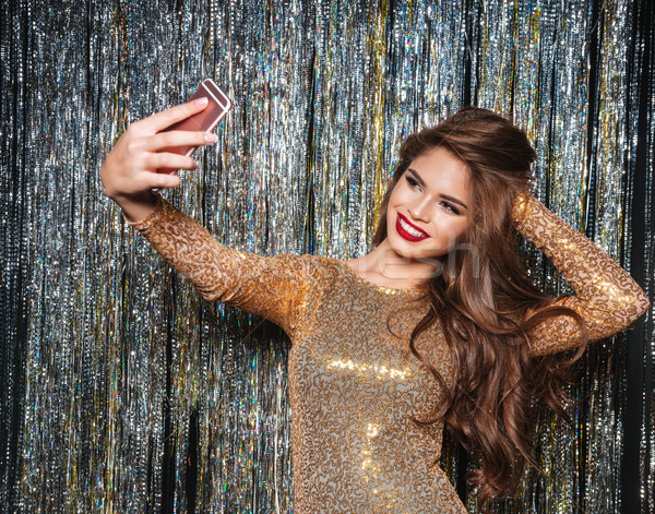 Smiling woman in evening dress taking selfie with mobile phone Stock photo © deandrobot