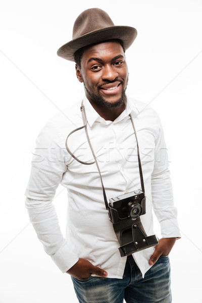Happy young african man wearing hat standing with camera Stock photo © deandrobot