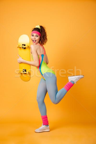 Alegre jóvenes mujer de la aptitud skateboard ejecutando Foto stock © deandrobot
