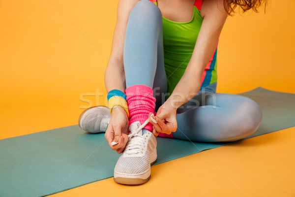 Closeup of sportswoman sitting on mat and tying shoelaces Stock photo © deandrobot