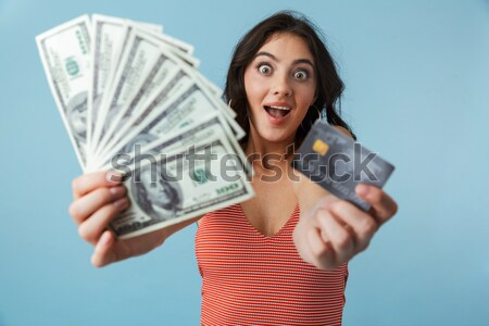 Beautiful young girl holding cash and credit card Stock photo © deandrobot