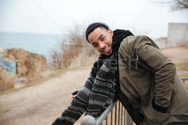Young handsome african man walking on the street. Stock photo © deandrobot