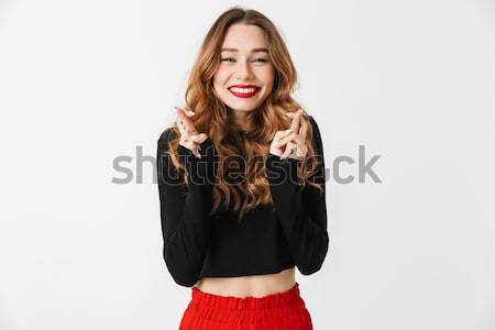 Playful woman with finger on cheek Stock photo © deandrobot