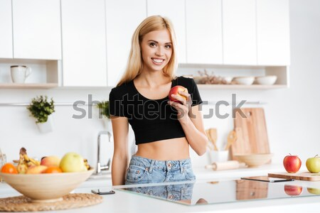 Smiling Blonde woman standing in kitchen Stock photo © deandrobot