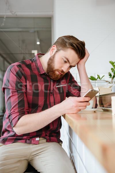 Zaklatott fiatalember okostelefon kávé étterem asztal Stock fotó © deandrobot