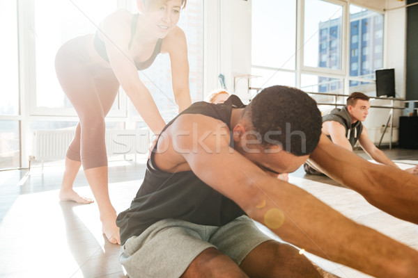 Man stretching and working out with trainer in yoga studio Stock photo © deandrobot